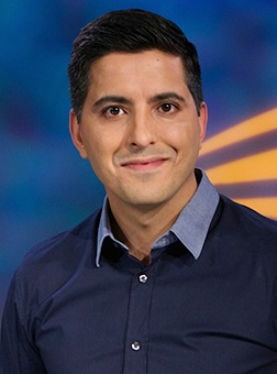 Image of a man with dark hair wearing a navy shirt. He is standing against a blue background and smiling into the camera