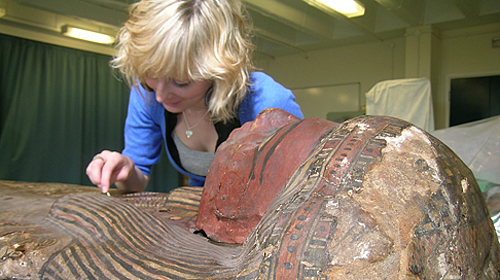 Female student cleaning the outside of an Egyptian coffin