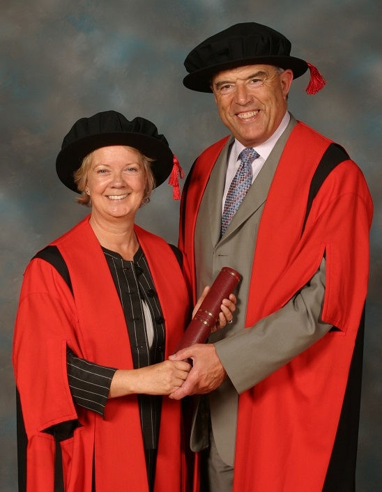 Image of a man and a woman holding hands and smiling into the camera